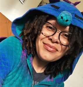 person with locks and light skin in blue and purple dragon pajamas