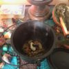 a black cauldron with burning herbs sits among crystals and tarot cards on an altar draped in turquoise ankara fabric.
